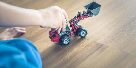 boy playing with a toy car on hardwood floors