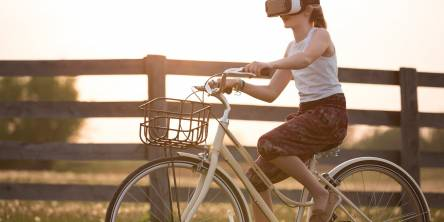 Girl wearing a vr box driving a bicycle