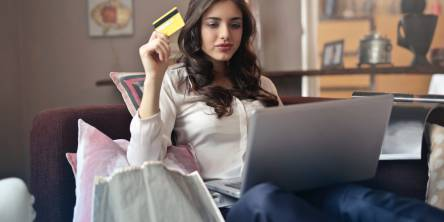 A woman is sitting on the couch looking at something a silver laptop and holding a bank card in her right hand.