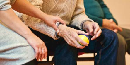 Three people sitting on a a bench. Two are elderly men and one is a woman. The middle man is holding a stress ball while the woman has her hand on his wrist.