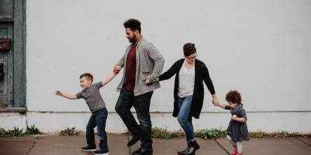 A family walking together consisting of a mother, father, son and daughter