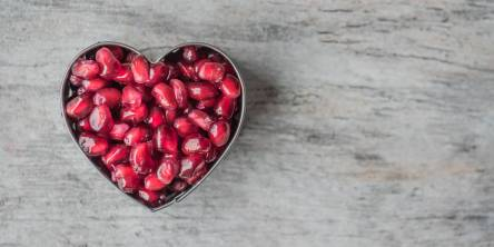 A heart made out of pomegranate seeds.