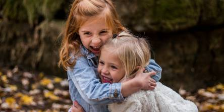 Two little girls outside hugging.