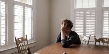 Man sitting alone at wooden dining table with his head leaning on his left hand, his elbow is on the table and he is facing a window