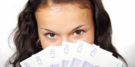 Woman looking at the camera with a fan of £20 notes.