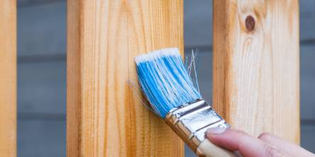 Man painting the slats of a wooden fence with a large paintbrush that has been dipped in blue paint.