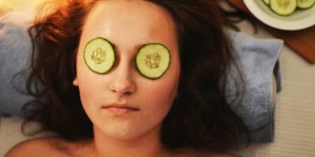 Woman laying down with cucumber slices over her eyes and a bowl of sliced cucumbers by her head on the right hand side.