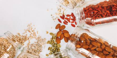 5 seeds and nuts that count as superfoods spilled on a while table