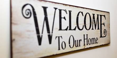 Wooden wall sign that reads 'welcome to our house'
