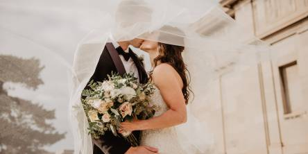 Bride and Groom kissing outdoors. The bride is holding a bouquet and their faces are covered by her veil. The groom's hand is on her hip facing the camera.