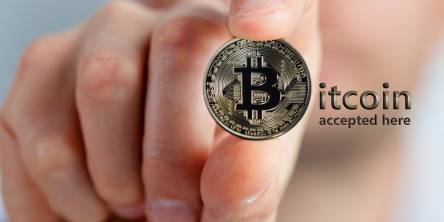 hand holding a bitcoin physical coin