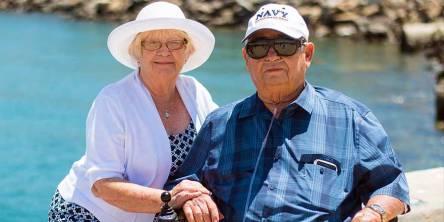 Senior couple sitting near beach shore