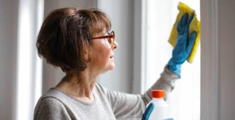 Older woman cleaning a window with a yellow cloth.