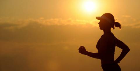 Woman jogging with the sunset in the background.