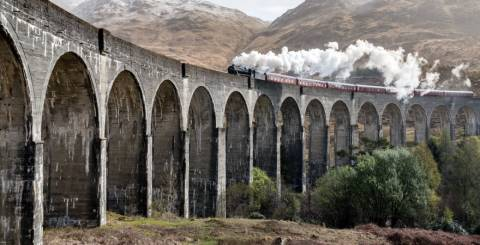 A side view of the Glenfinnan Viaduct in Scotland with a train passing over the top.
