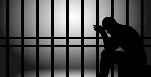 man sitting in jail